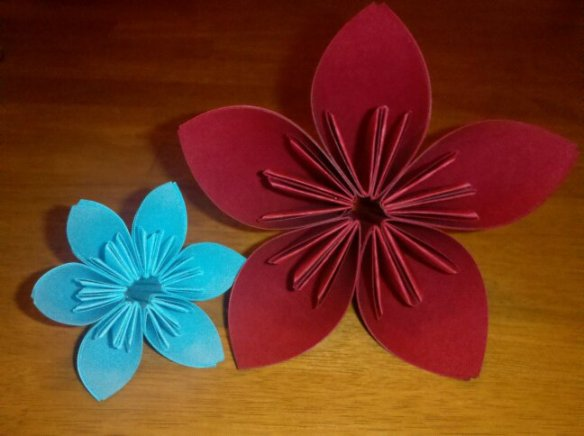 a small, light blue paper flower next to a larger, deep red paper flower